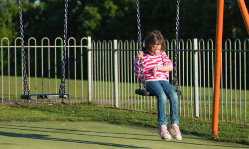 kid on swing looking a wrist watch